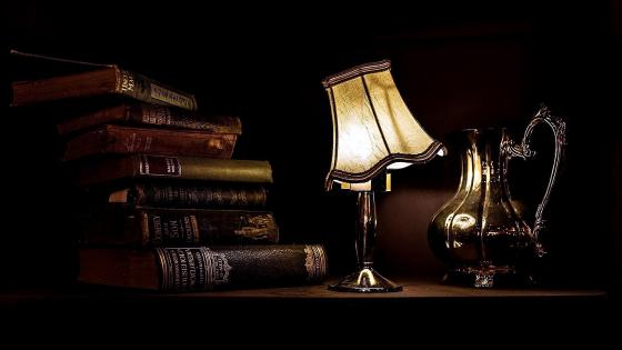 Old books on table with lantern wallpaper