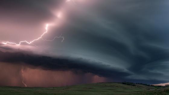 Pink lightning strikes over the field wallpaper
