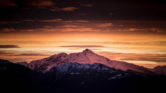 Orange sky over the snowy mountain wallpaper