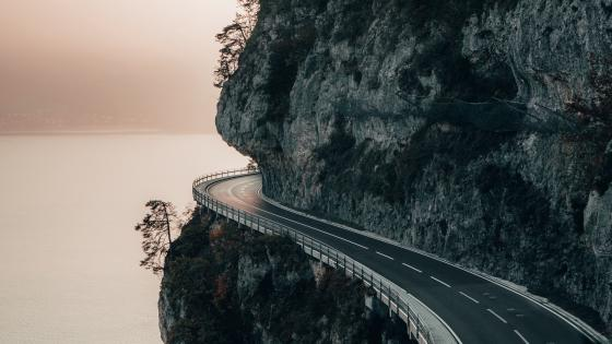 Dangerous road next to the rock wall wallpaper