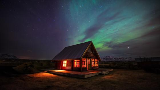 Cottage in Iceland under the polar lights wallpaper