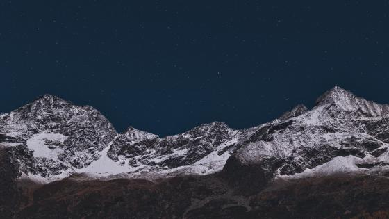 Starry sky over the rugged mountains wallpaper
