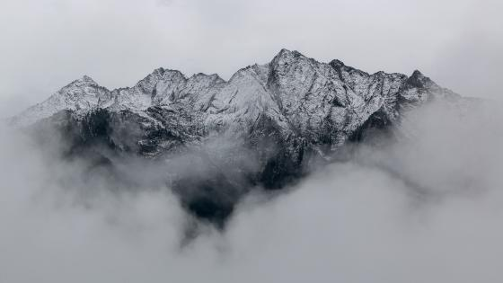 Snowy mountain in the clouds wallpaper