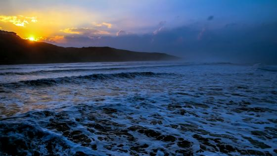 Foamy sea waves at sunset wallpaper