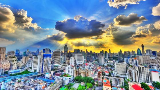 Rays of sunlight bursting through clouds above Bangkok City wallpaper