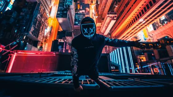 Neon masked guy climbing building wallpaper