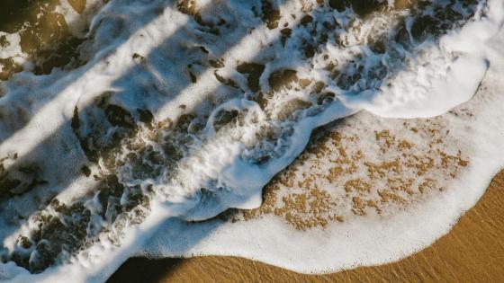 Foamy waves from above wallpaper