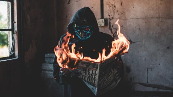 Neon masked guy burning newspaper wallpaper