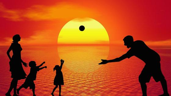 Dad And Mom Play Ball With Their Children On The Sea At Sunset wallpaper